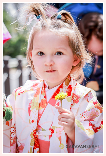 A girl in Kimono with a dandelion in her hands