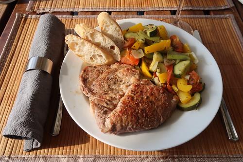 Gegrilltes Schweinenackensteak zu mediterranem Gemüse und Baguette