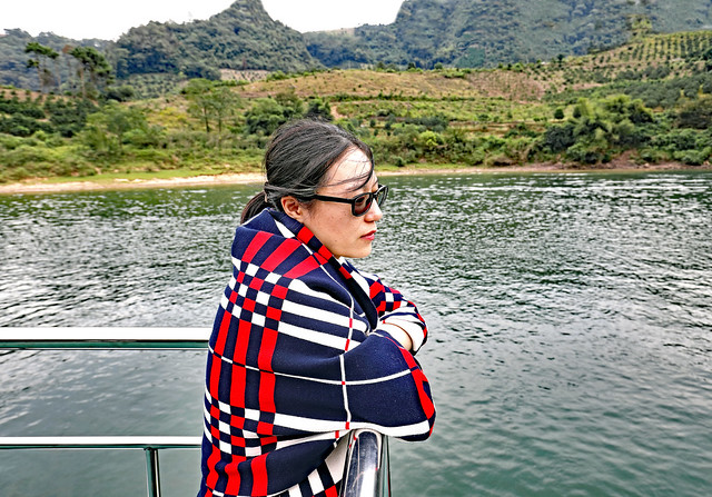 China October 2017. Li River (Xing'an). Pensive young woman in colorful cape with geometric patterns.