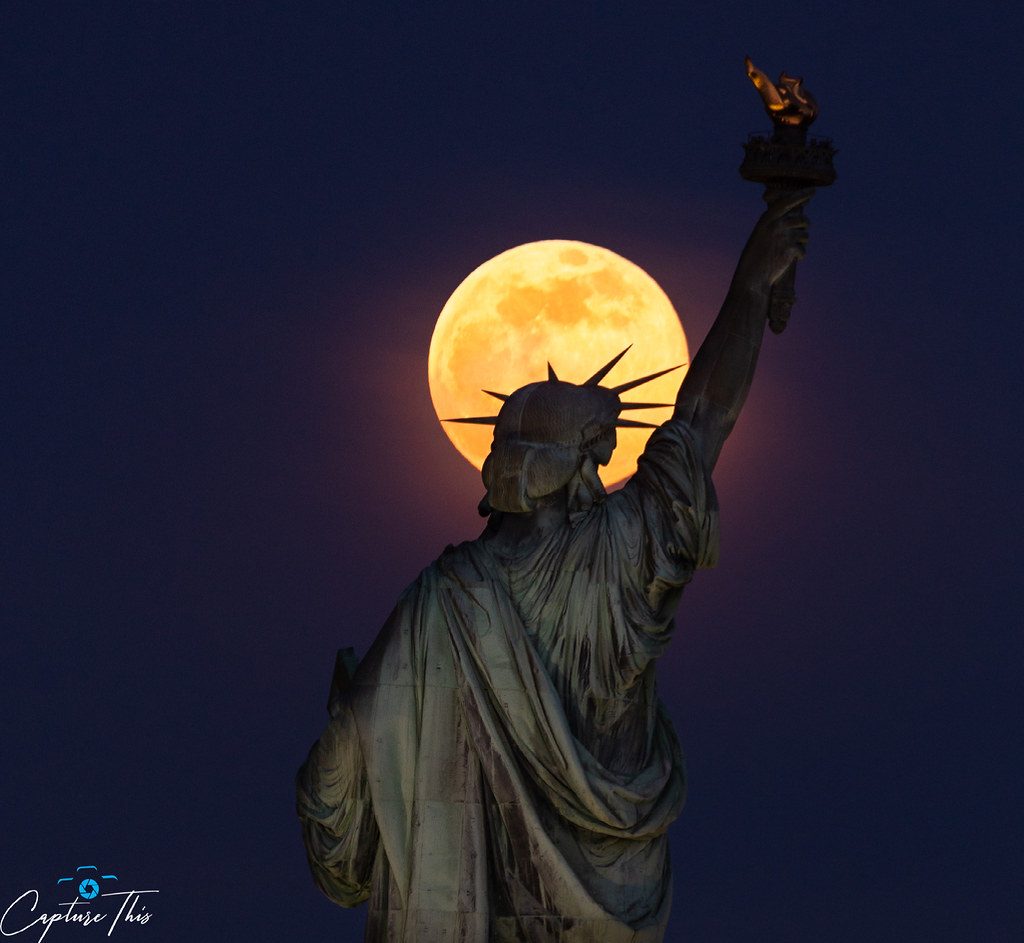 The pink supermoon rises in front of the Statue of Liberty on Monday April 26th, 2021.