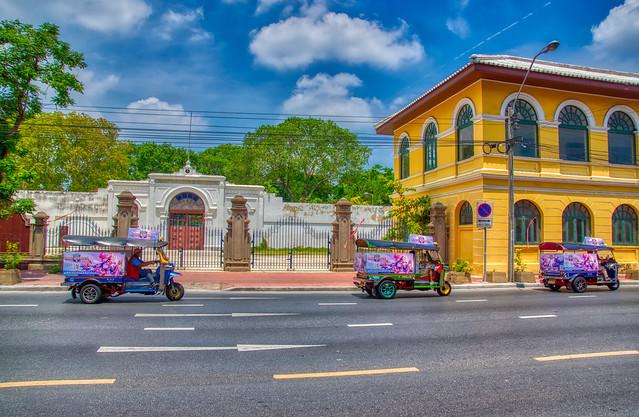 Tuk Tuks passing Bangkok Corrections Museum on Maha Chai road on Rattanakosin island (Old Town) in Bangkok, Thailand