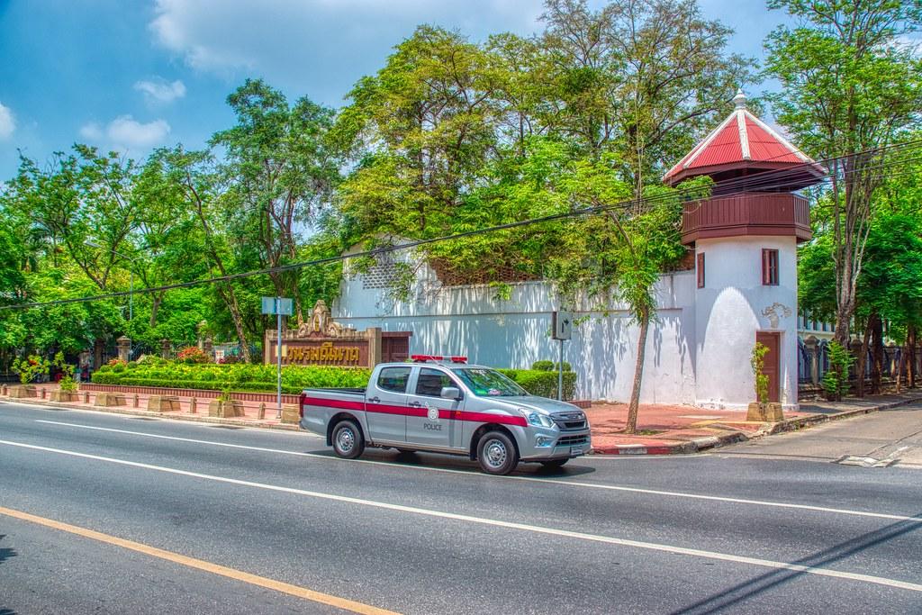 Police car passing the northeast corner of Rommaninat park on Rattanakosin island (Old Town) in Bangkok, Thailand