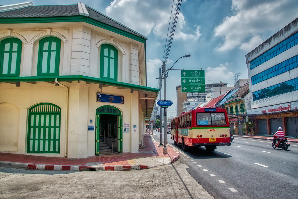 Bus passing the exit of Sam Yot MRT (subway) station on Charoen Krung road on Rattanakosin island (Old Town) in Bangkok, Thailand