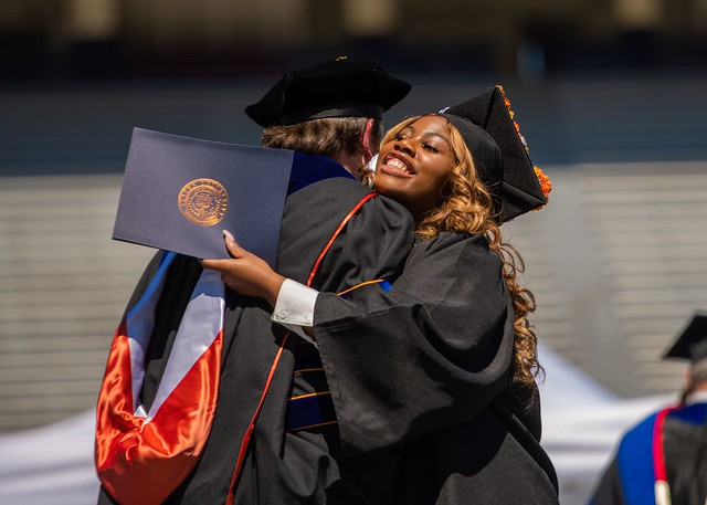 An Auburn graduate hugs her college's dean on stage during commencement at Auburn University.