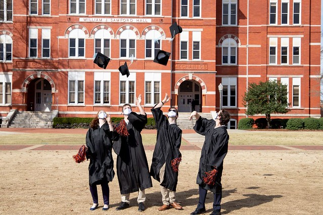 Auburn's EAGLES program students toss their caps in front of Samford Hall.