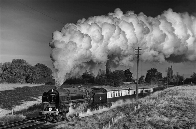 BR Standard 9F 2-10-0 no. 92203 hauls a passenger train comprised of blood and custard carriages towards Woodthorpe bridge