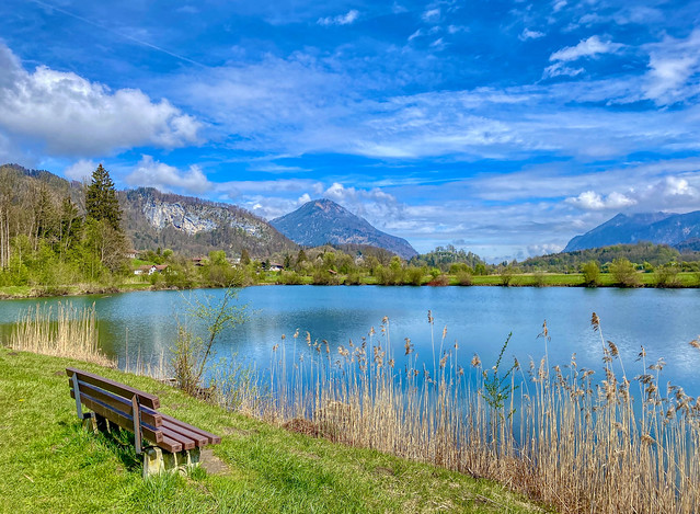 Bench by lake Kreutsee with Wildbarren and Kranzhorn mountains in Bavaria, Germany