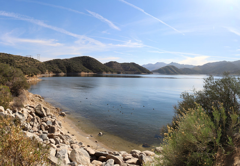 A sandy beach on the shore of Silverwood Lake, with the dam in the distance right of center
