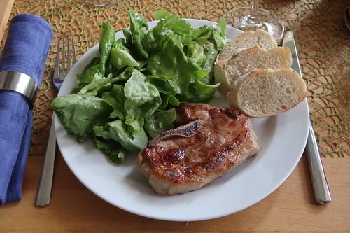 Gegrillte Lammbeinscheibe mit grünem Salat und Baguette
