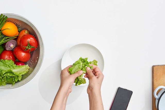 Top view of a woman hand preparing a fresh vegetarian salad with organic vegetables