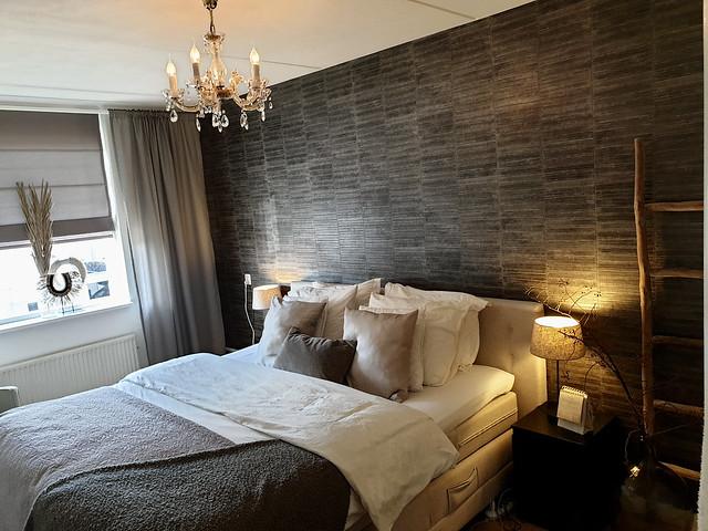 Landelijke slaapkamer behang hotel chique veren en schelpen ornament vensterbank houten ladder
