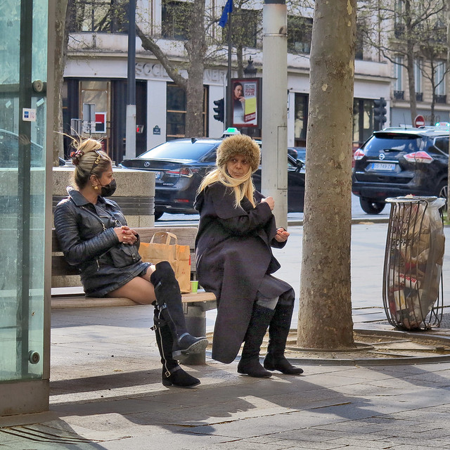 Mother and daughter in high black boots, sitting on a bench in the Champs Elysees
