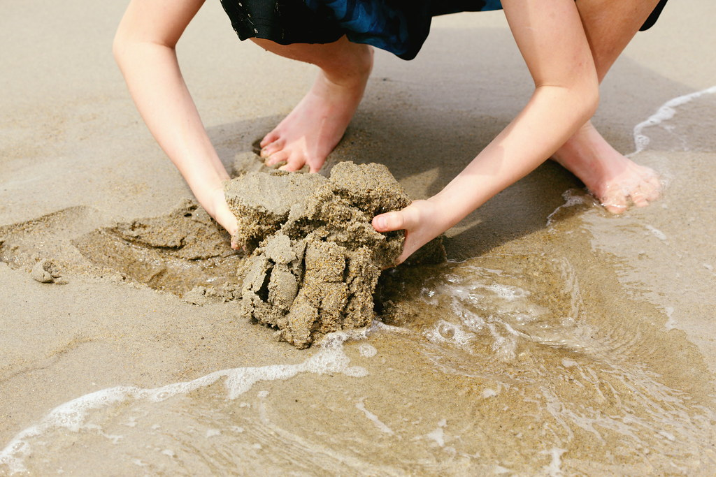 Child Digging in Wet Sand