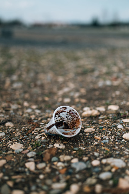 Close-up of the dirty plastic cup with coffee dregs thrown on the ground
