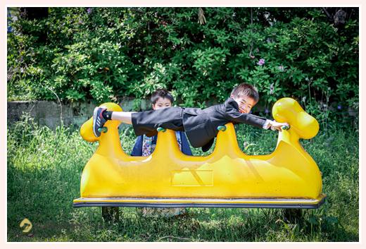 公園のシーソーで遊ぶ男の子