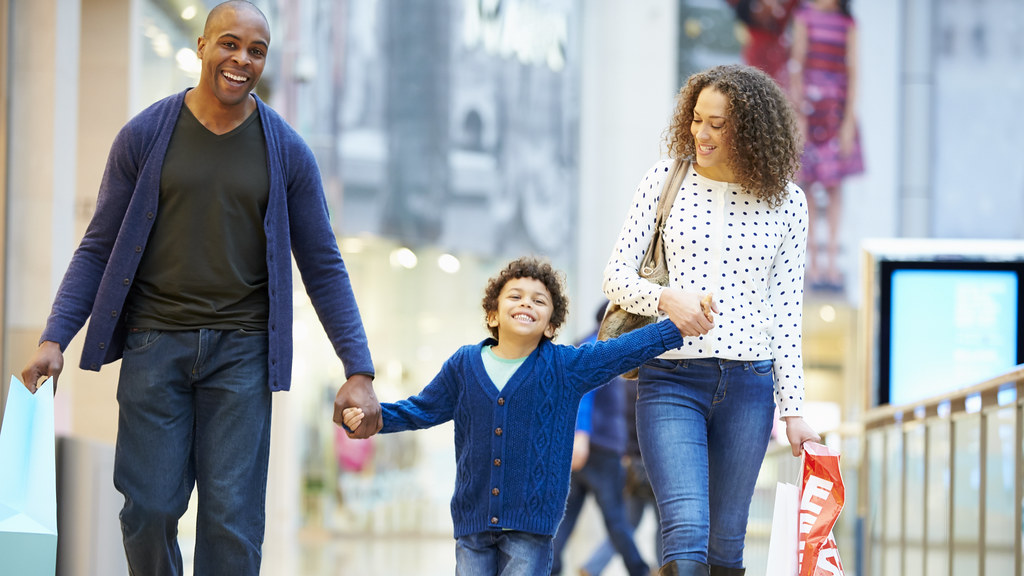 Image of family, mother and father with child in shopping centre.