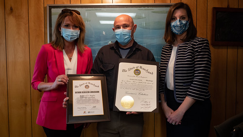 Photo of secretaries Schultz and Riccio presenting certificates to  Backwater Angler owner Theaux Le Gardeur