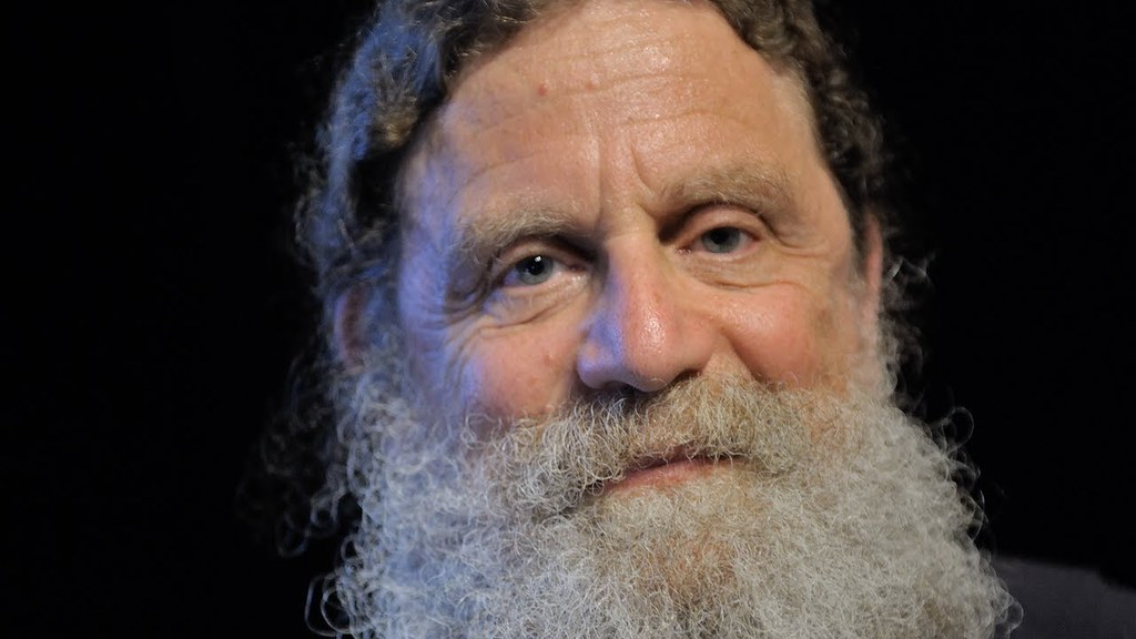 A photo portrait of Robert Sapolsky. He has blue eyes, and very bushy grey beard and long, tightly curled brown hair