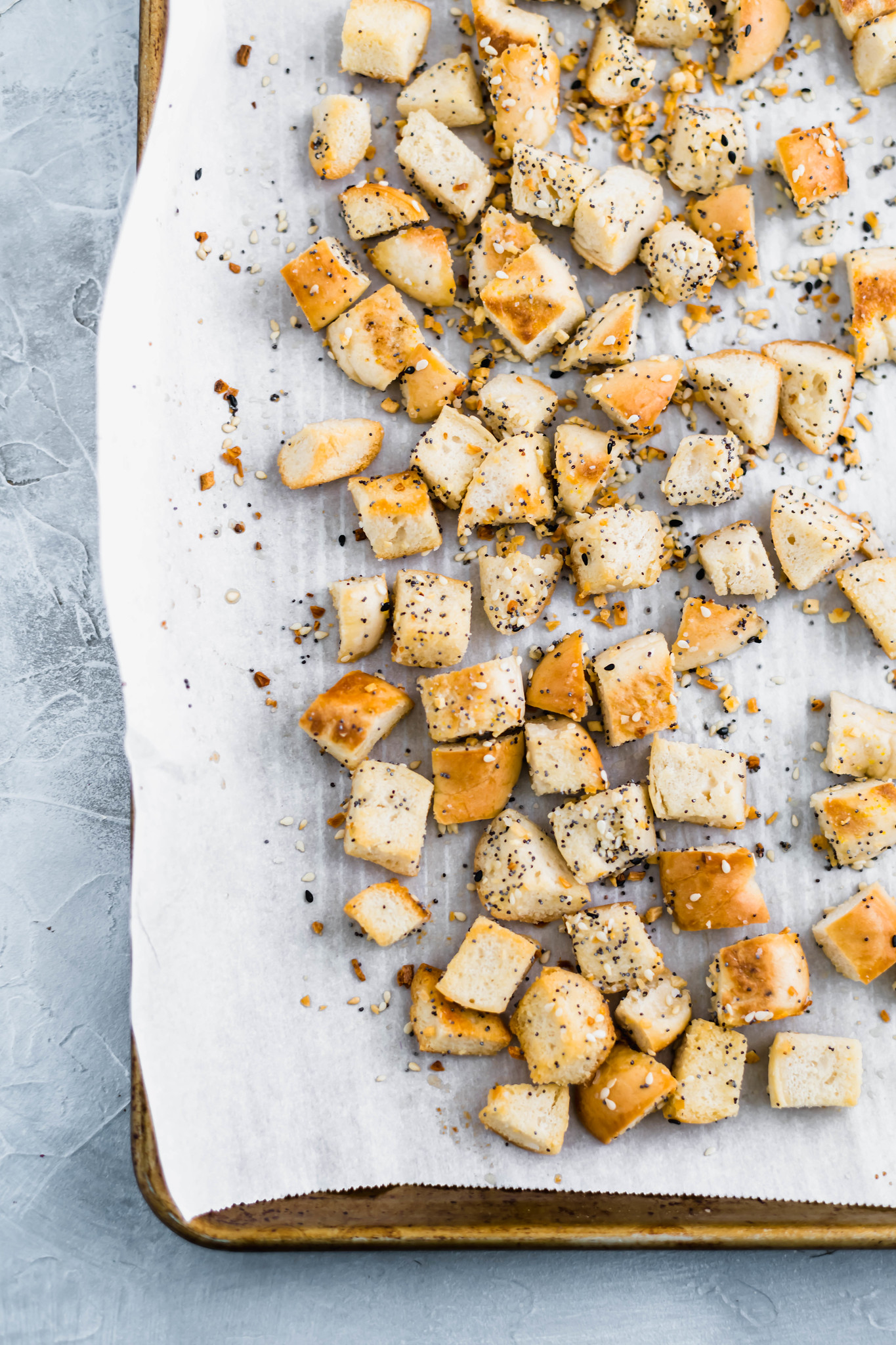 Everything bagel croutons on a baking sheet lined with parchment paper.