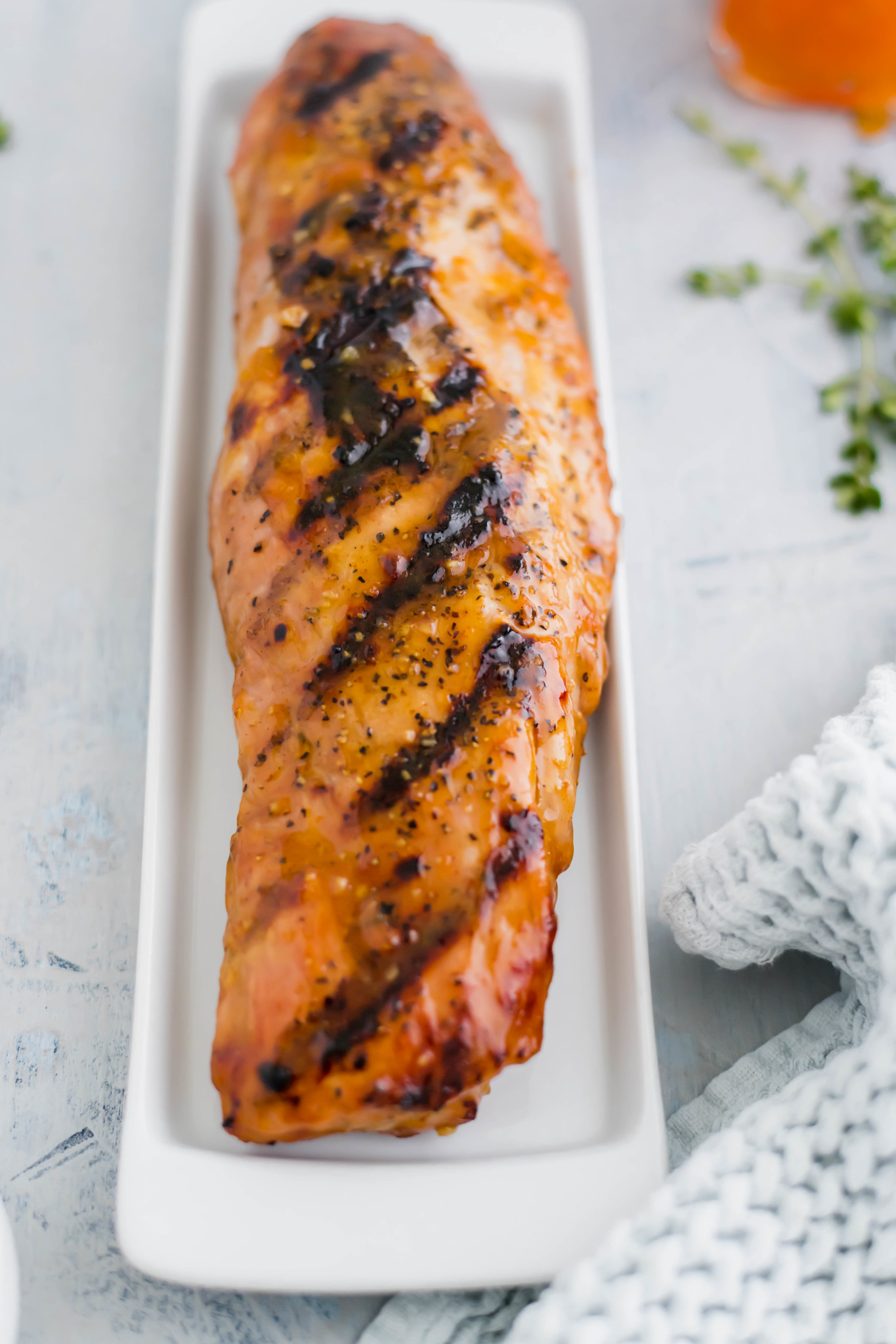 whole apricot glazed pork loin on a skinny white plate. Dried apricots and sprigs of thyme in top right corner.