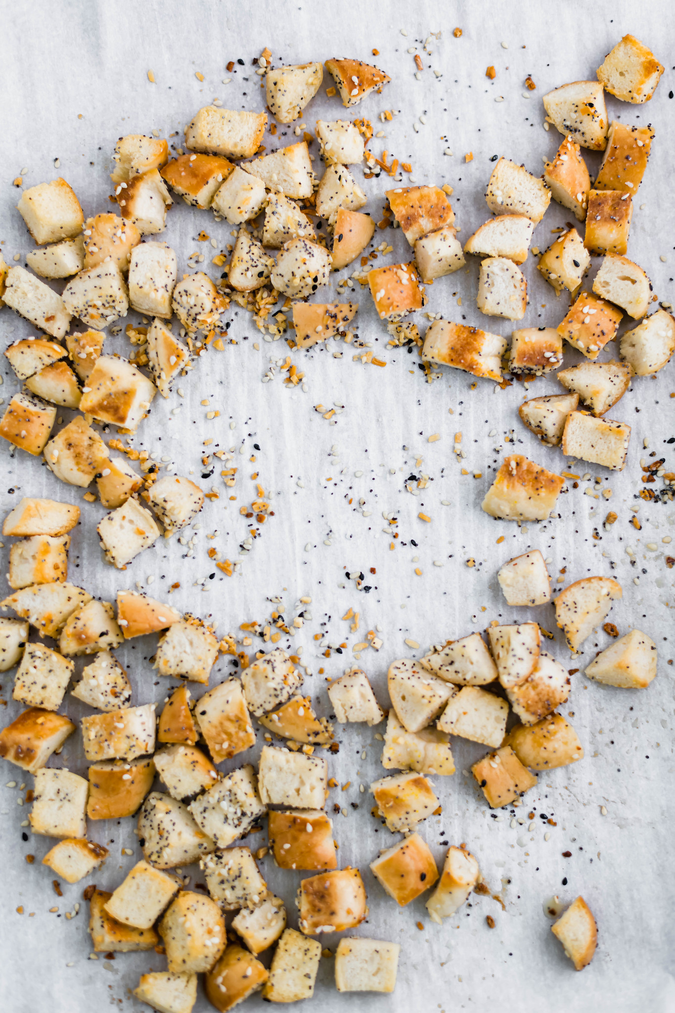 Everything bagel croutons spread out on a parchment lined baking sheet.