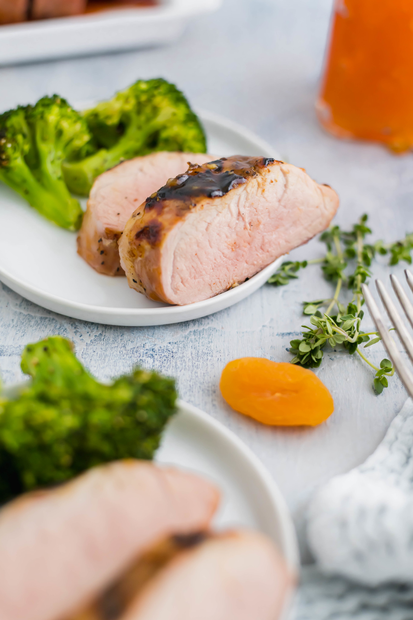 Close up of slice of apricot pork tenderloin with a fork, dried apricot and sprig of thyme in the bottom right corner.