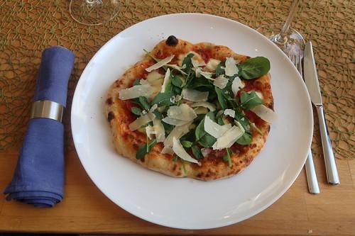 Pizza mit frischen Tomaten, scharfer Salami, Parmesan und Rucola