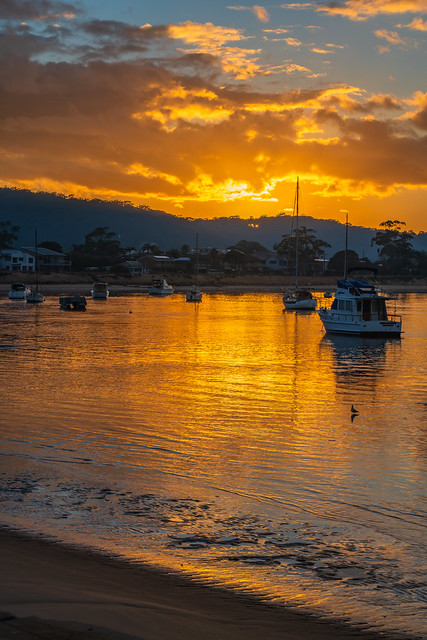 Golden sunrise waterscape with boats and cloud cover