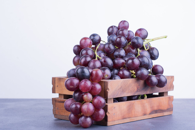 Red grapes in a wooden tray on blue background