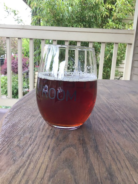 Immersion brewing's Raise The Alarm red IPA, in glass on table, outside
