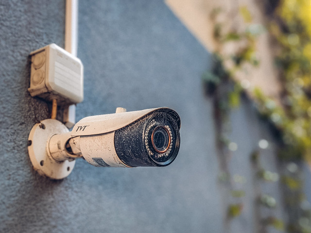 Surveillance camera on a building wall recording the activity in a pedestrian area