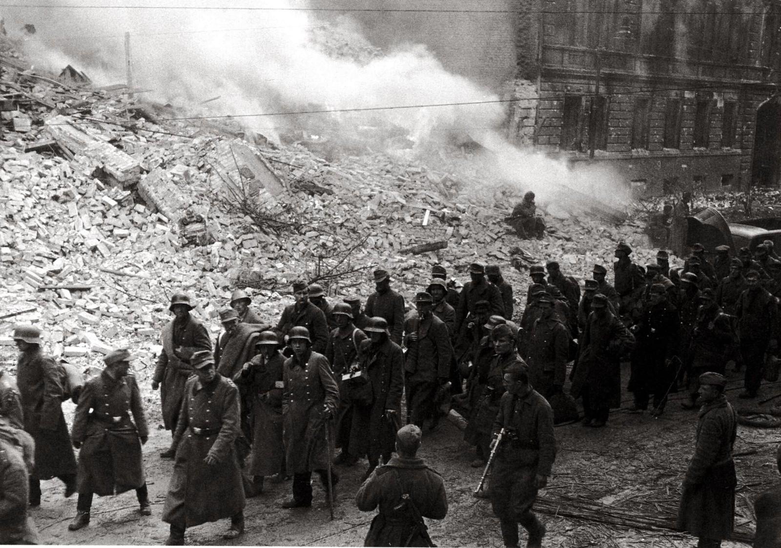 11. Советские солдаты ведут немецких военнопленных по истерзанным войной улицам Берлина
