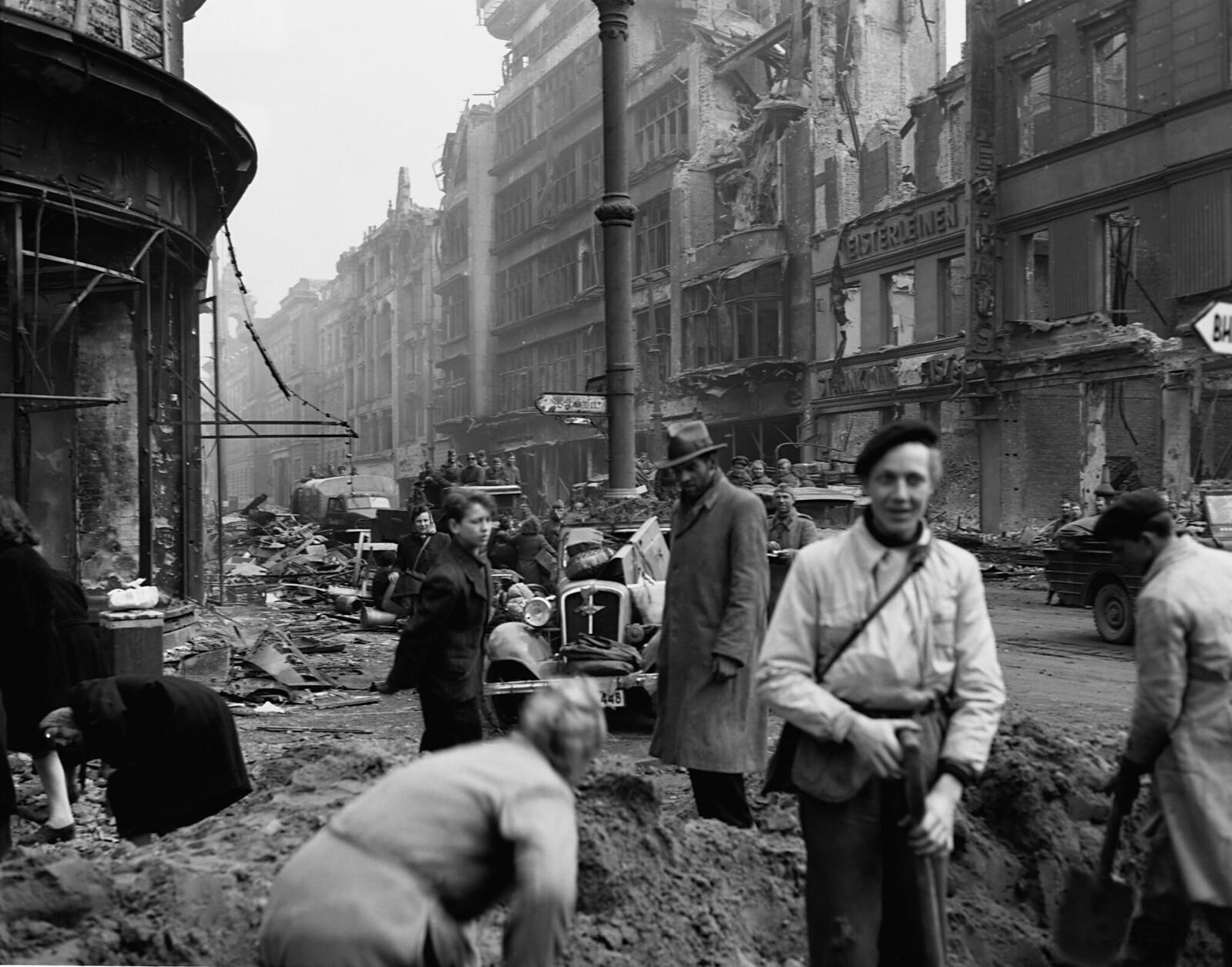 27. Знаменитая улица Унтер-ден-Линден в Берлине сильно пострадала от бомбардировок и обстрелов. Под руководством советских солдат мирные жители расчищают завалы для пешеходов и автотранспорта