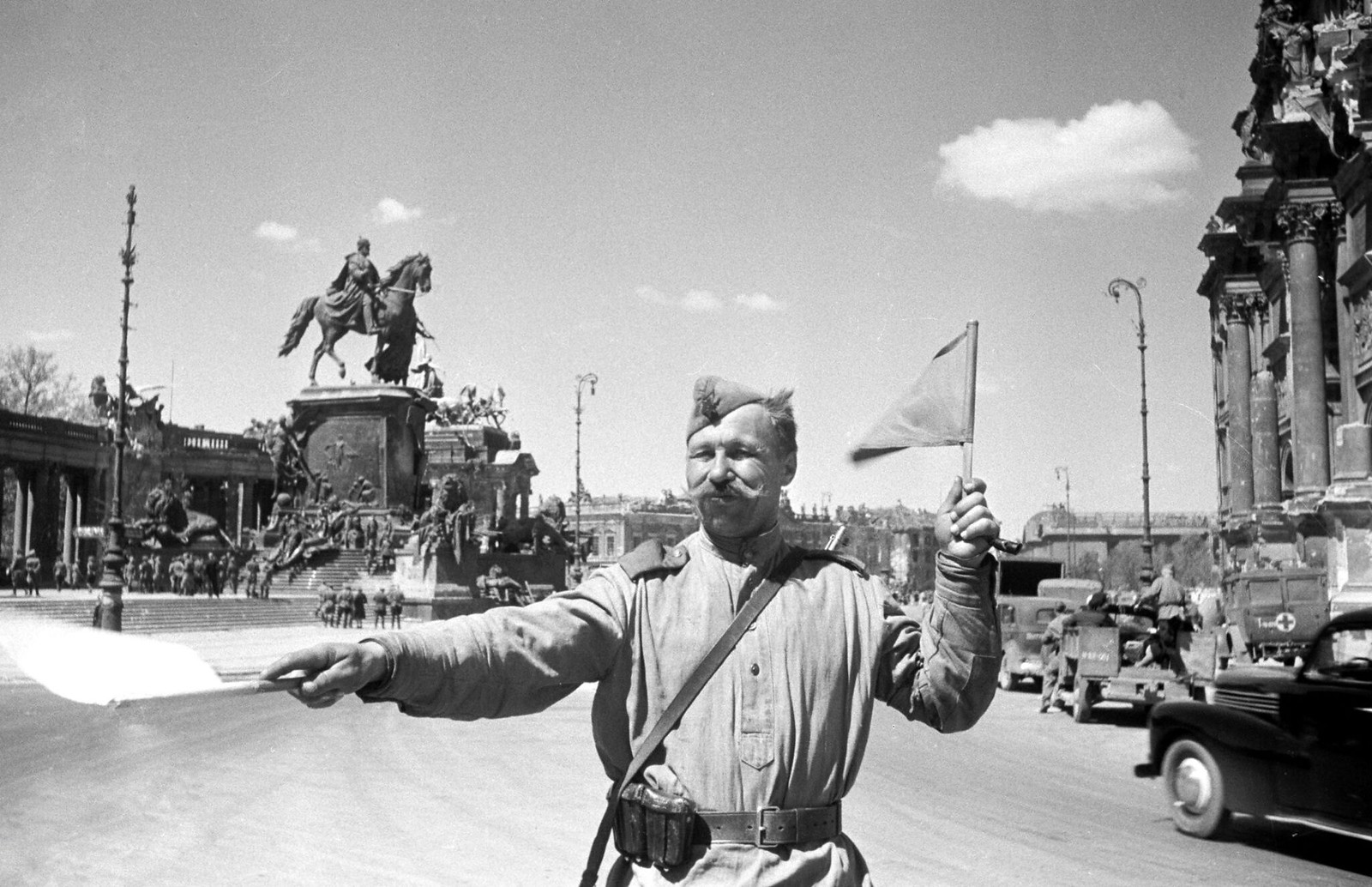 16. Советский солдат, контролирующий движение на улице Берлина
