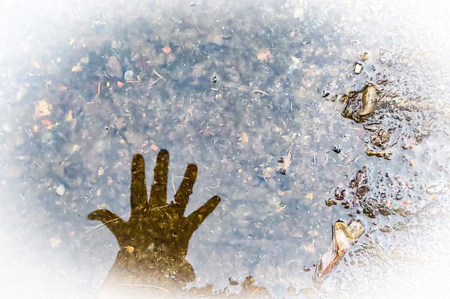 Spegling av min hand i vattenpölen