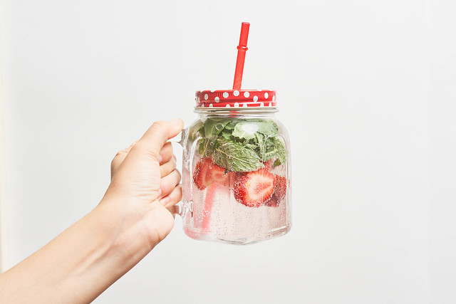 Female hand holding a jar of cold summer fruit cocktail