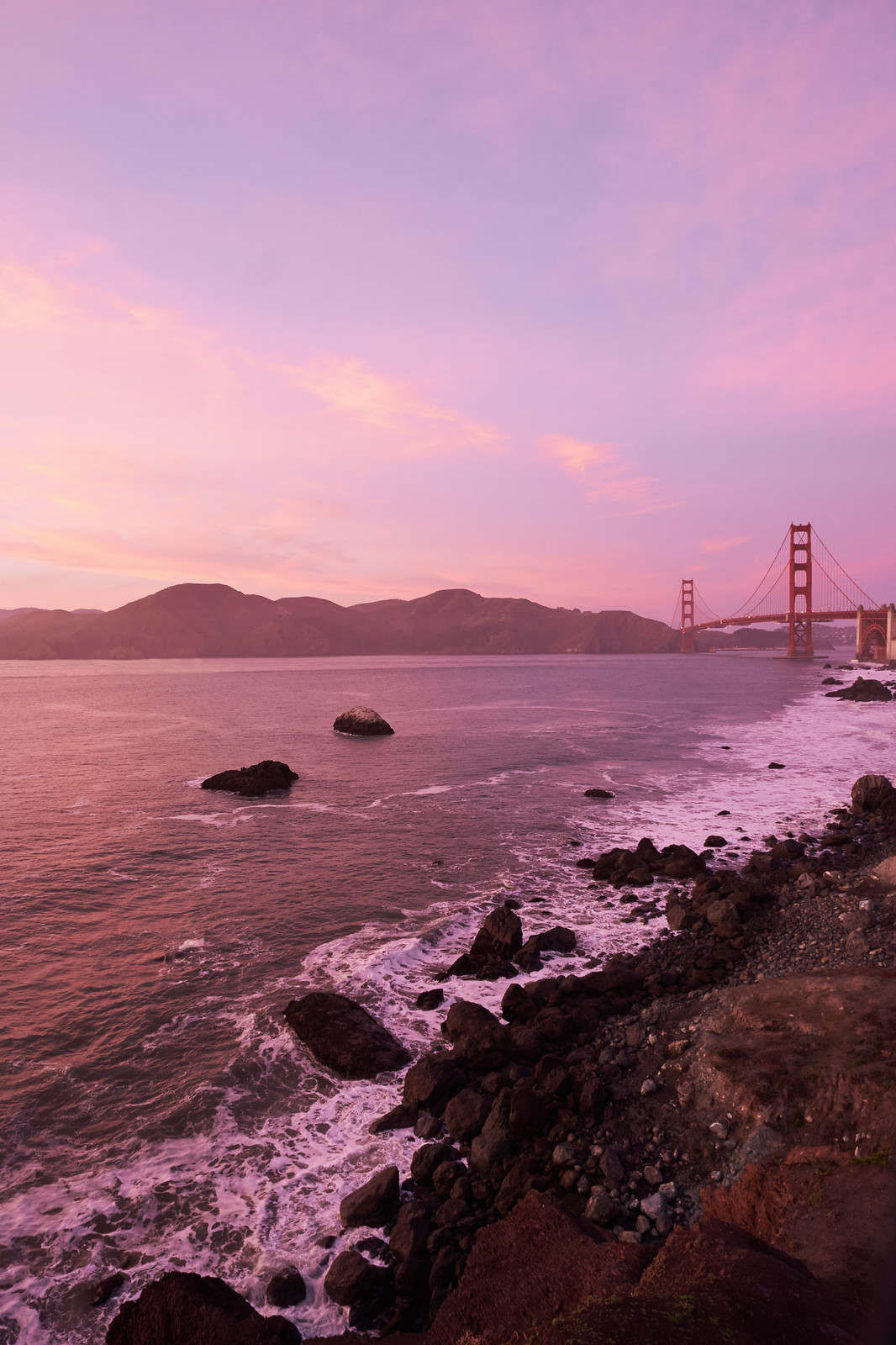 The golden-gate bridge at sunset with a golden-red sky.