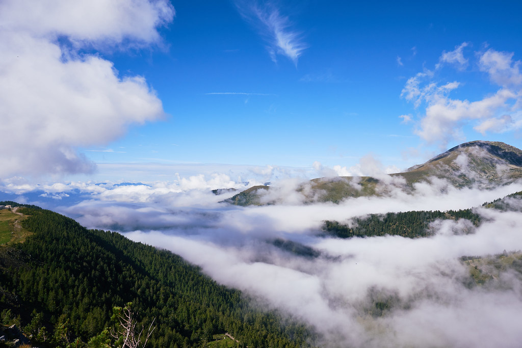 Overlooking a mountain range that is hidden by low-hanging fog clouds.