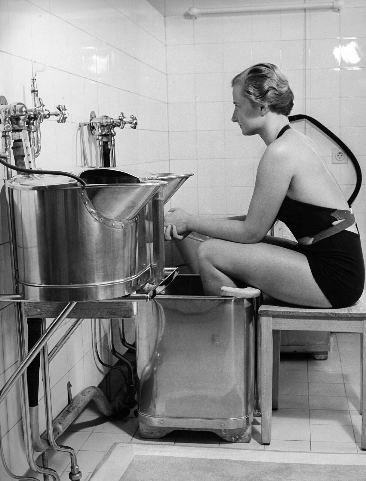 08. Гидротерапия. Молодая женщина держит ноги в водяной бане для стимуляции кровообращения
