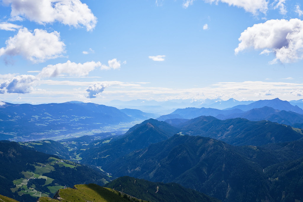 Looking into a valley in southern austria on a sunny day with a couple of clouds in the sky.
