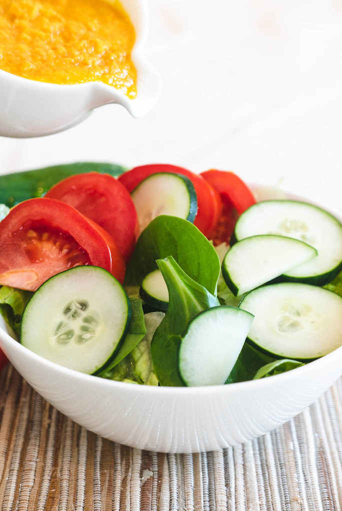 A photo of a salad. Wafu dressing is being poured over salad.