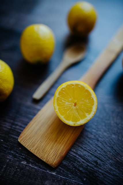 A slice of lemon on a mixing spoon. Smaller wooden spoon and three lemons in a blurry background.