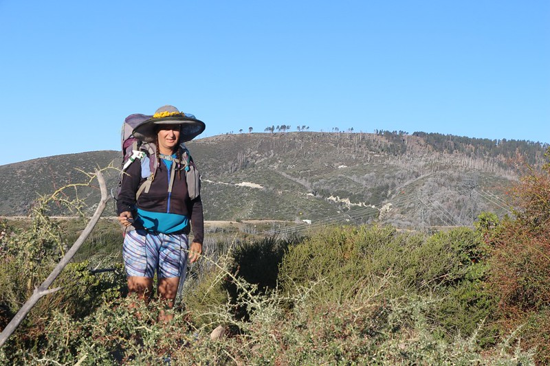 Vicki, ready to hike in the morning, with Mount Gleason behind her and buckthorn plants in the foreground