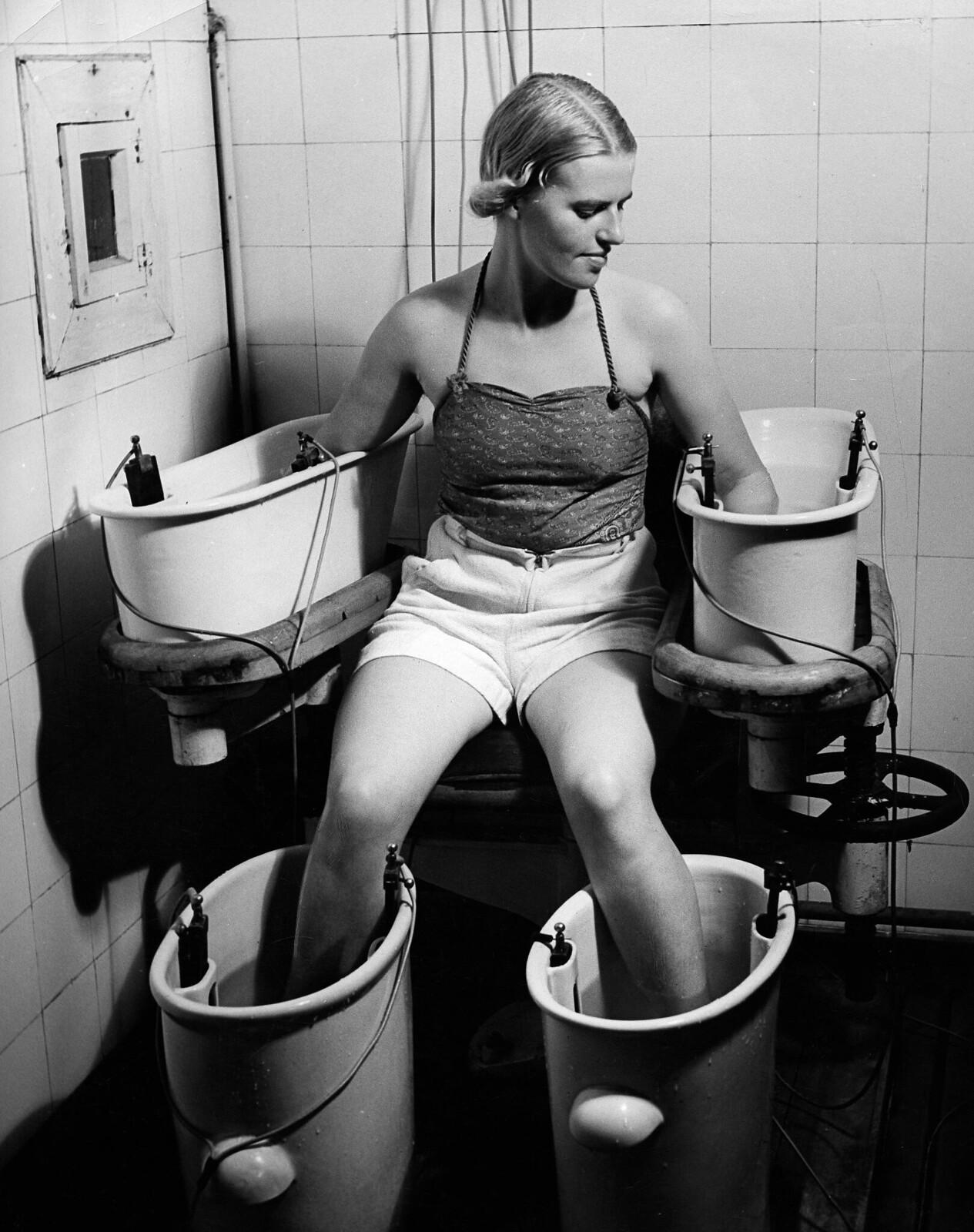 11. Четырехэлементная гальваническая ванна. Женщина держит руки и ноги в четырех электрических водных ваннах, эта процедура положительно влияет на кровообращение