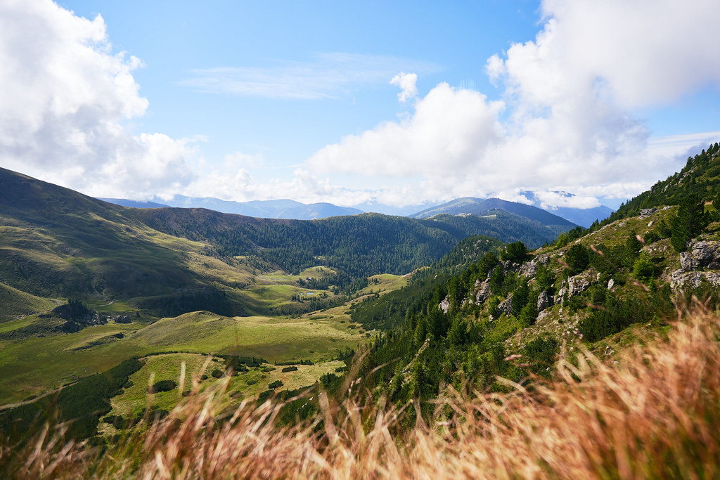 A small valley between two higher mountain ridges. Orange grass in the foreground blurry through the depth-of-field.