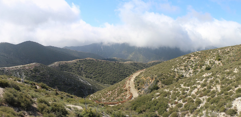 View from the PCT with Santa Clara Divide Road below, and Iron Mountain in the clouds across the way