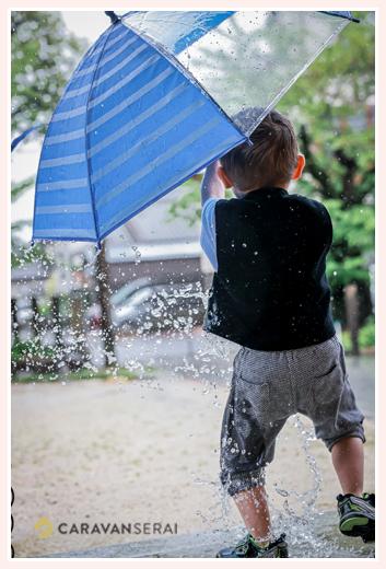 傘を持った小さな男の子の後ろ姿