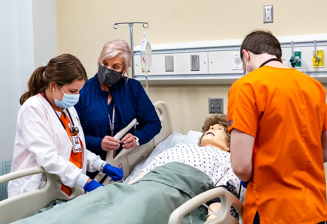 A senior nursing student provides care for a simulated patient