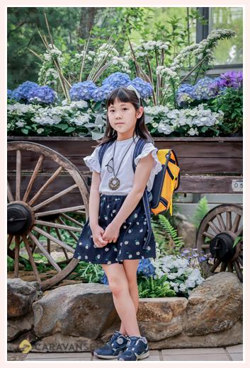 ランドセルを背負った女の子 お花の前でポーズ
