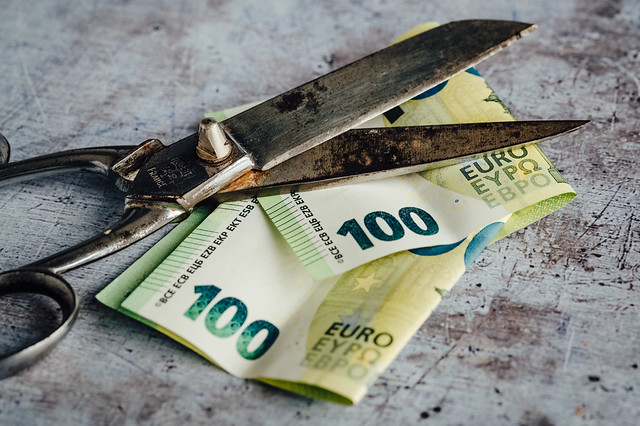 Old rusty scissors and two 100 euro bills on a wooden surface